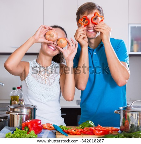Young couple preparing dinner with vegetables and having fun at kitchen