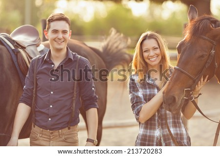 Young couple preparing their horses for a ride on a rural farm - stock photo