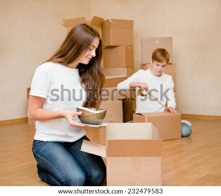 Young couple puts things in cardboard boxes for moving into a new home - stock photo