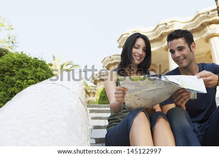 Young couple reading map while sitting on steps - stock photo