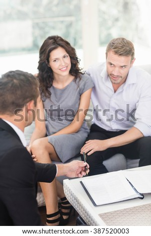 Young couple ready to buy new house interacting with estate-agent - stock photo