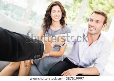 Young couple ready to buy new house shaking hands with estate-agent - stock photo