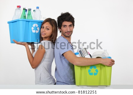 Young couple recycling bottles - stock photo