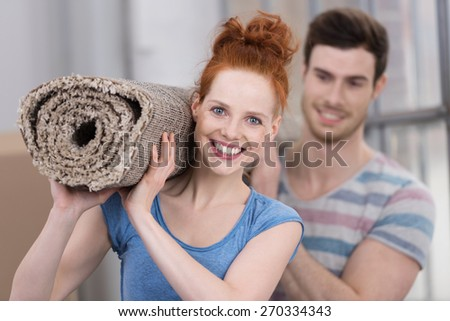 Young couple redecorating the house carrying a rolled up new carpet for the living room with focus to the smiling redhead woman - stock photo