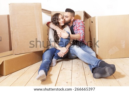 young couple relaxes and kisses after the move - stock photo