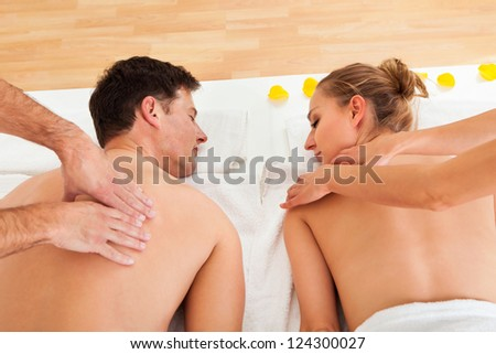 Young couple relaxing and enjoying a joint back massage at a spa and the woman is surrounded by yellow flower petals - stock photo