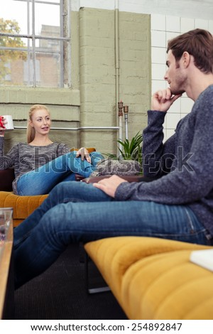 Young couple relaxing at home chatting on the sofas in the living room as they spend a restful day in their apartment, low angle view - stock photo