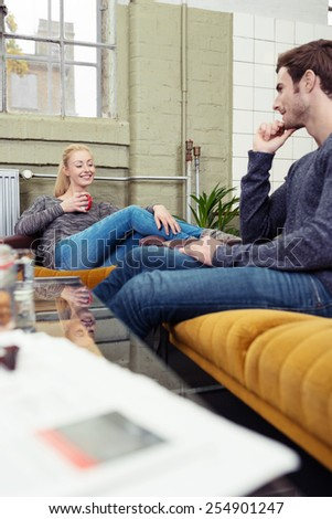 Young couple relaxing at home over coffee sitting on the settees in their living room laughing and smiling at each other - stock photo