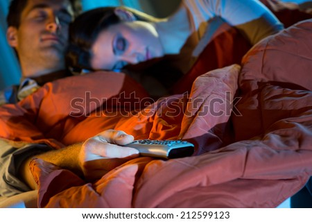 Young couple relaxing at home with blanket in front of TV. - stock photo