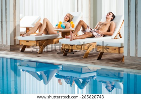 Young couple relaxing at swimming pool - stock photo