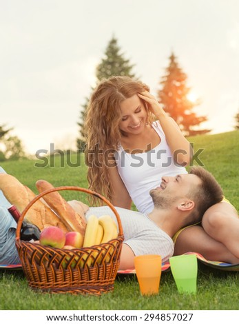 Young couple relaxing in picnic in the sunset. Man lying on his girl-friend's knees and smiling to her, basket and cocktails standing near. - stock photo
