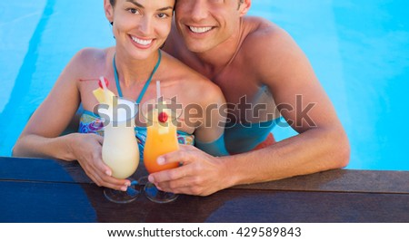 young couple relaxing in resort swimming pool and drinking cocktails - stock photo