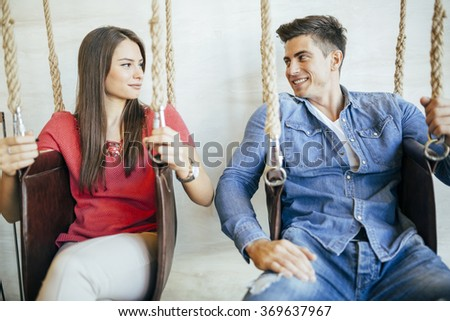 Young couple relaxing in swing while talking and flirting - stock photo