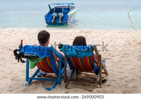 Young couple relaxing in the lounge chairs on the sand sea beach - stock photo