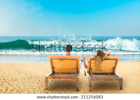Young couple relaxing lying down on a beach chair - stock photo