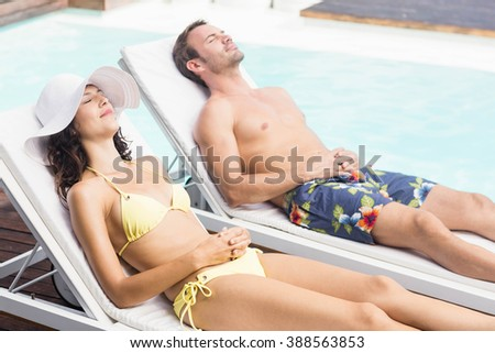Young couple relaxing near swimming pool enjoying holiday - stock photo