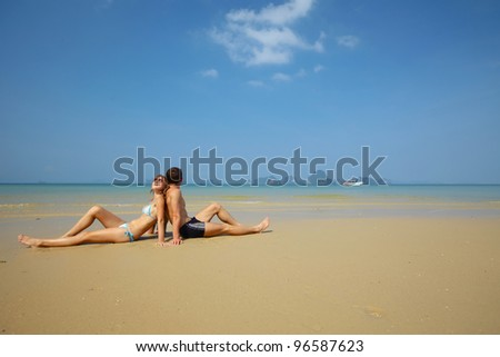 Young couple relaxing on a perfect tropical sand - stock photo