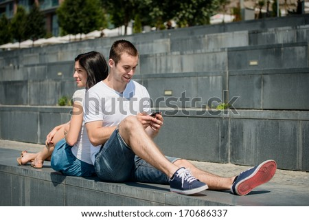 Young couple relaxing outdoor in street - man with smartphone - stock photo