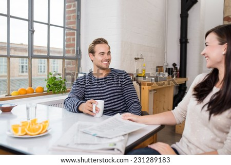 Young couple relaxing over breakfast sitting at a table in their apartment smiling and chatting together - stock photo