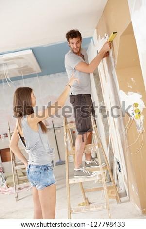 Young couple renovating home, DIY, measuring. - stock photo