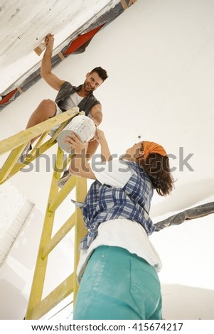 Young couple renovating home diy. Woman passing painting to man on top of ladder. - stock photo