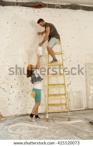 Young couple renovating home, man painting wall on top of ladder, woman lifting painting can up. - stock photo