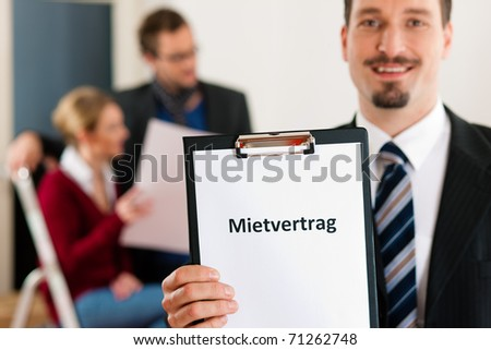 Young couple renting a home or apartment, they are meeting the owner or real estate broker standing in front (the sign is written in German) - stock photo