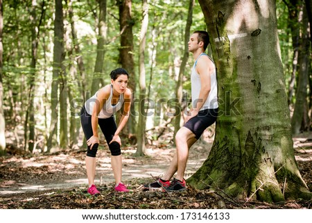 Young couple resting after jogging in a forest, man leans against tree - stock photo