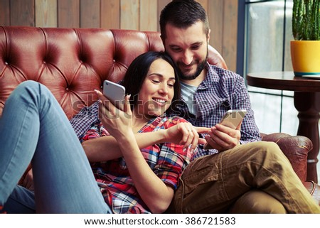 young couple resting on sofa and looking at smartphone - stock photo