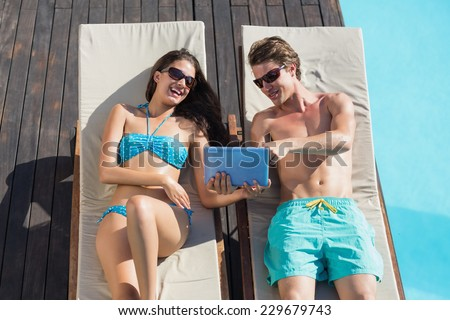 Young couple resting on sun loungers while using digital tablet by swimming pool - stock photo