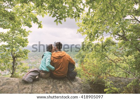Young couple resting on top the mountain. Toned Image. - stock photo