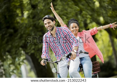 Young couple riding on the bicycle - stock photo