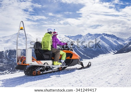 Young couple riding snowmobile snow mountain road - stock photo