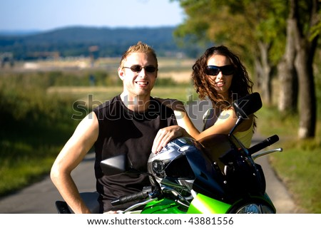 young couple riding the motorcycle - stock photo
