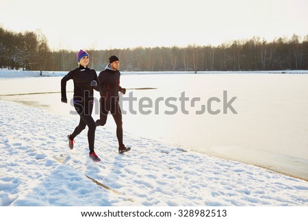 Young couple running during winter - stock photo