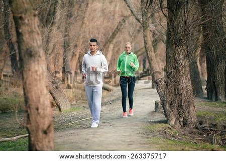 Young couple running in nature - stock photo