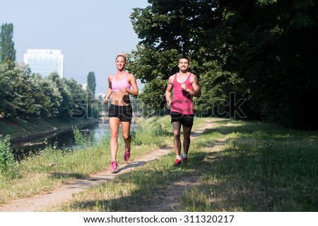 Young Couple Running In Wooded Forest Area - Training And Exercising For Trail Run Marathon Endurance - Fitness Healthy Lifestyle Concept - stock photo