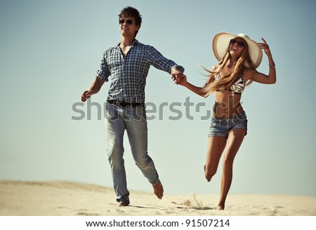 Young couple running on beach. - stock photo