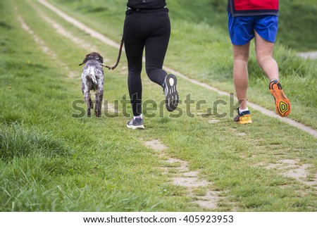Young couple running with dog outdoors in nature blurred motion - stock photo