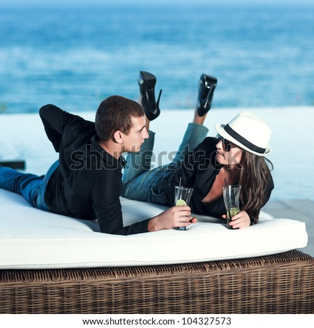 Young couple. Sea on the background - stock photo