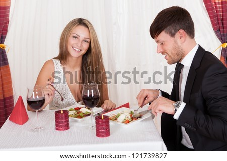 Young couple seated at a restaurant table enjoying a romantic dinner by candlelight and drinking red wine - stock photo