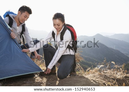 Young couple setting up the tent - stock photo