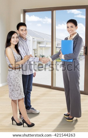 Young couple shaking hands with a real estate agent after discussions at new home - stock photo