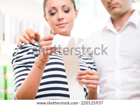 Young couple shopping at store and examining a long grocery receipt. - stock photo