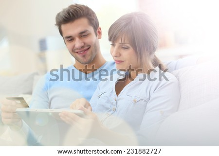 Young couple shopping on internet with tablet - stock photo