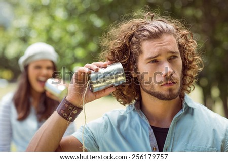 Young couple shouting through tin cans on a summers day - stock photo