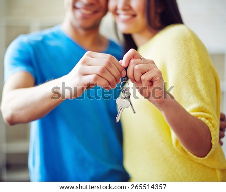 Young couple showing key from new house - stock photo