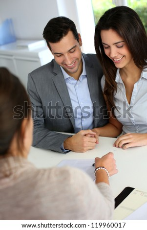 Young couple signing financial contract - stock photo