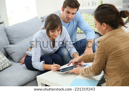 Young couple signing financial contrat on digital tablet - stock photo