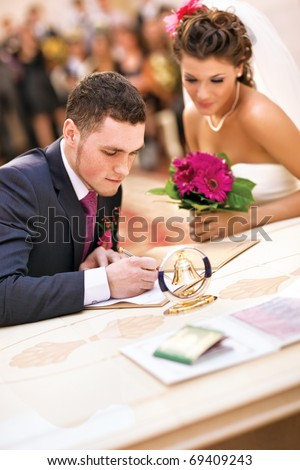 Young couple signing wedding documents. Focus on hand. - stock photo